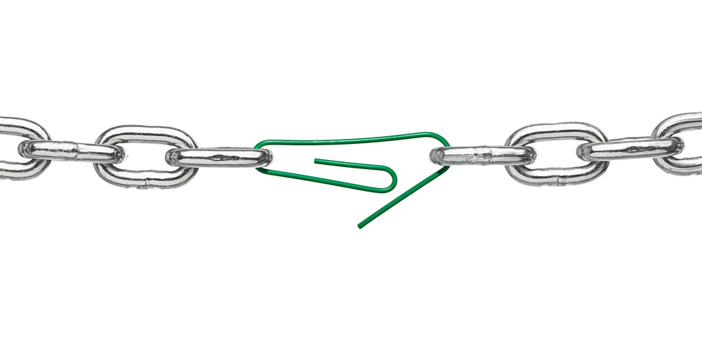 close up of a broken chain and a paper clip on white background.jpeg